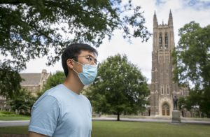 A duke student wearing a mask walks by Duke Chapel