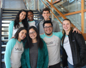 Americorp vista volunteers with Salud tshirts pose on a staircase