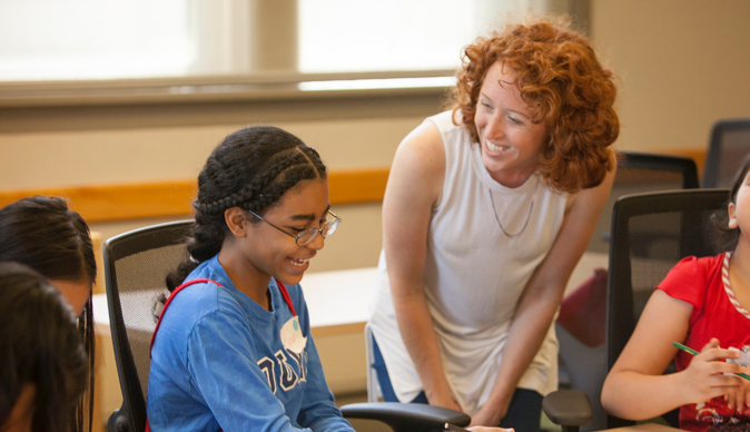 A smiling woman stands next to a young student doing work.