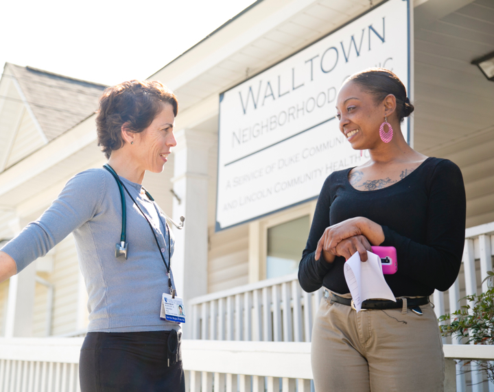 Two women speak outside of the walltown clinic