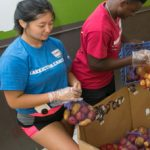 College students sort and pack potatoes at a food bank