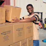 A volunteer helps stack boxes at a million meals event