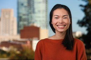 A headshot of Chi Vo with Durham skyline