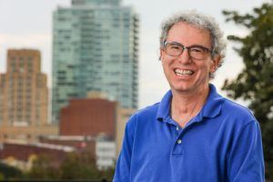 A headshot of David Stein with Durham skyline