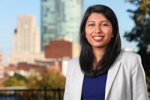 A headshot of Girija Mahajan with Durham skyline