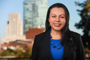 A headshot of Sandra Martinez-Zuniga with Durham skyline
