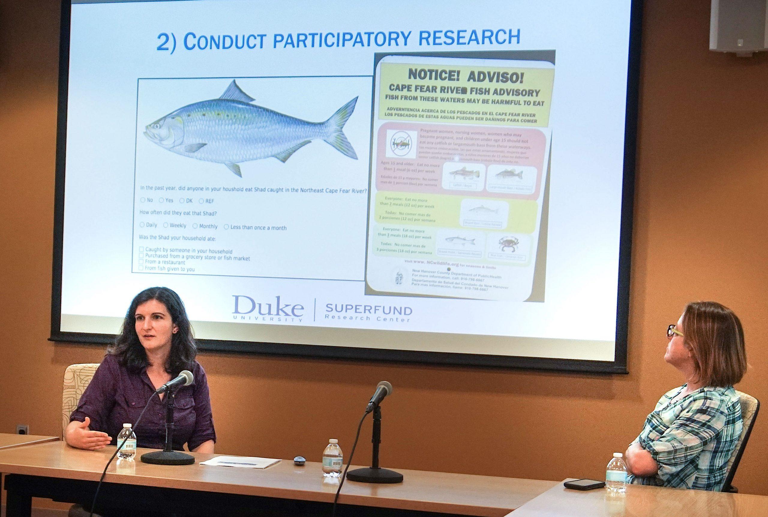 Duke faculty giving a power point presentation at a talk