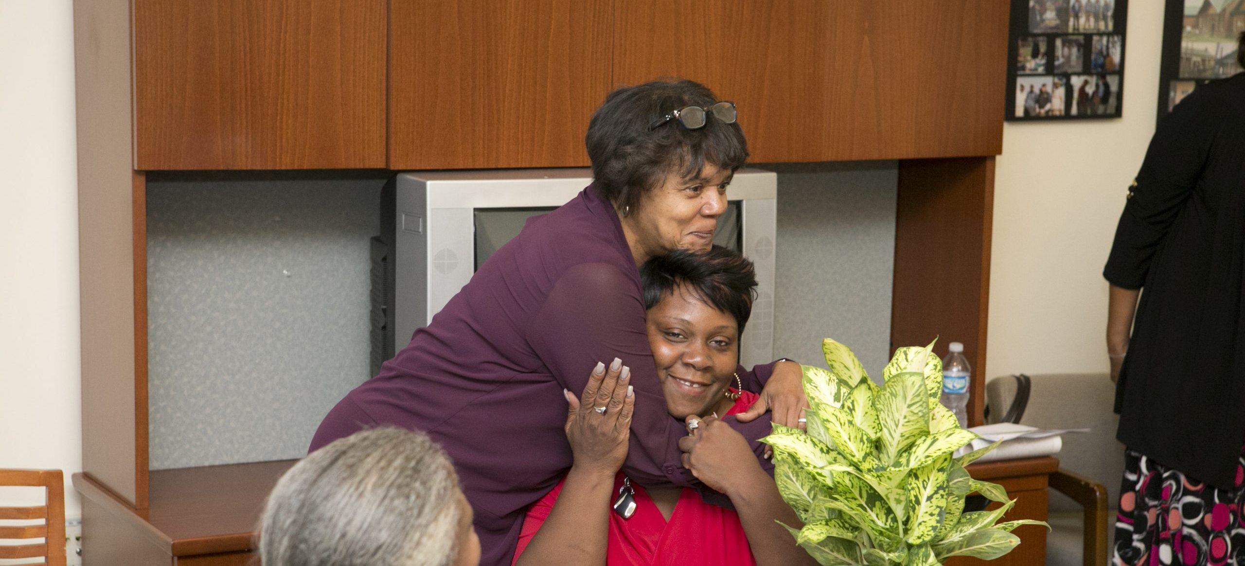 A Duke staff person hugs a homebuyers club member