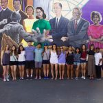 A group of Duke students stand in front of a Durham mural during a tour