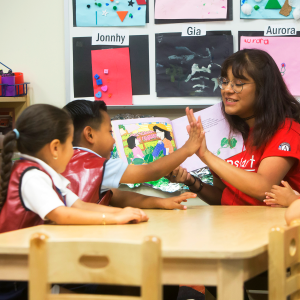 Jumpstart employee high fives a young child while reading to kids in a class